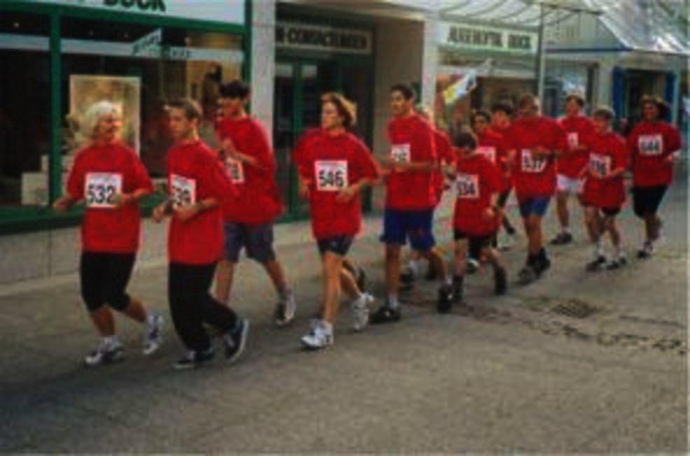 Schülerinnen und Schüler joggen paarweise durch die Innenstadt