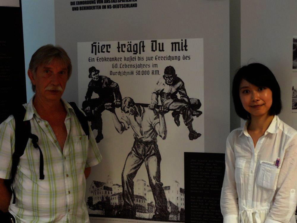 Udo Dittmann und Aiko Kino vor dem bekannten Bild über Kosten-Nutzen-Rechnungen bezüglich der Behinderten